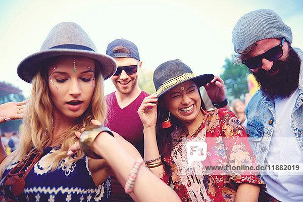Vier junge erwachsene Freunde in Fedoras tanzen auf dem Festival
