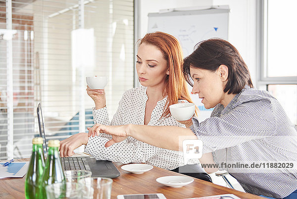 Businesswomen with coffee having discussion in meeting