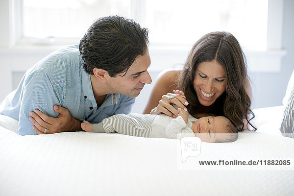 Mother and father leaning on bed  looking at newborn baby boy