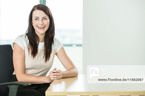 Porträt einer Geschäftsfrau am Schreibtisch sitzend  lachend