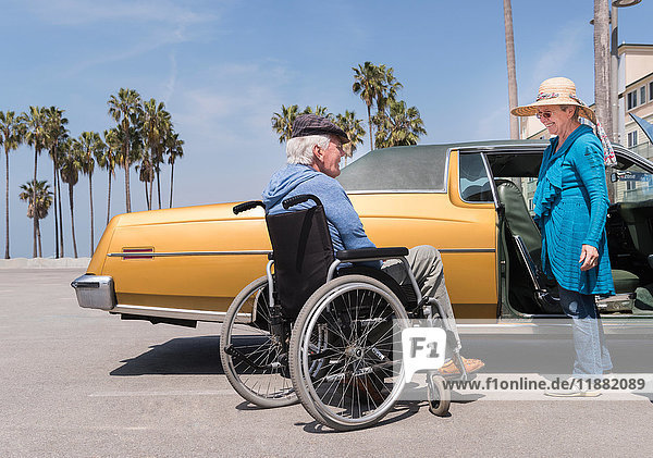 Senior woman chatting to husband in wheelchair by vintage car at Venice Beach  California  USA