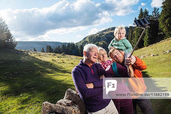 Drei-Generationen-Familie in ländlicher Umgebung  Selfie  mit Smartphone und Selfie-Stick  Genf  Schweiz  Europa