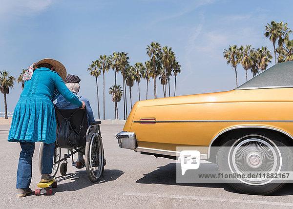Senior woman pushing husband in wheelchair by vintage car at Venice Beach  California  USA