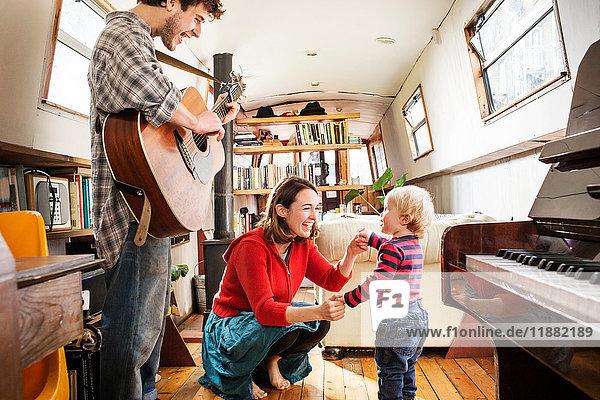 Familie mit einem kleinen Jungen  der auf einem Lastkahn lebt  Gitarre spielt und tanzt