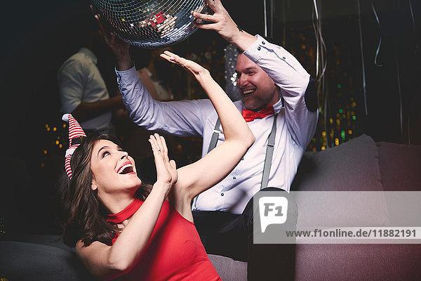 Mann und Frau treiben sich auf einer Party herum  Mann hält Discokugel über dem Kopf der Frau