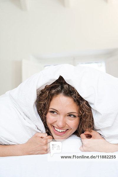 Woman lying on bed underneath quilt smiling