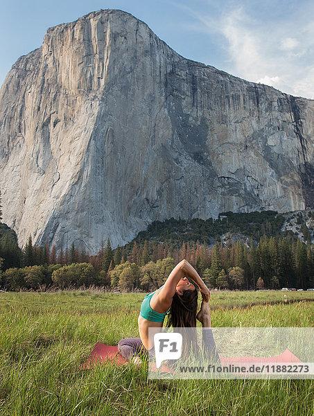 Yoga praktizierende Frau  die sich im Tal im Yosemite-Nationalpark  Kalifornien  USA  nach hinten gebeugt hat