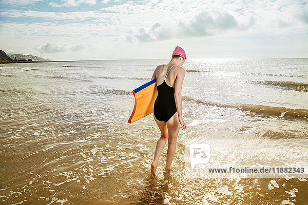 Young woman carrying surfboard in sea  Folkestone  UK