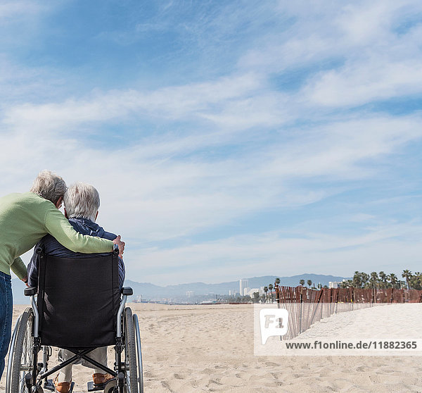 Rear view of senior man in wheelchair with wife looking out from beach  Santa Monica  California  USA