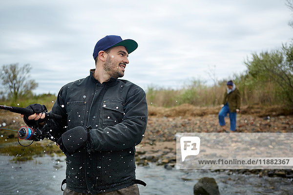 Junger Mann wird beim Hochseefischen vom Meer bespritzt
