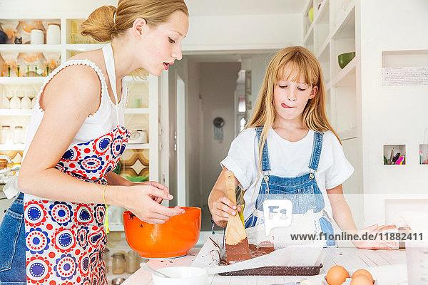 Mädchen bereiten in der Küche Schokoladen-Brownies zu