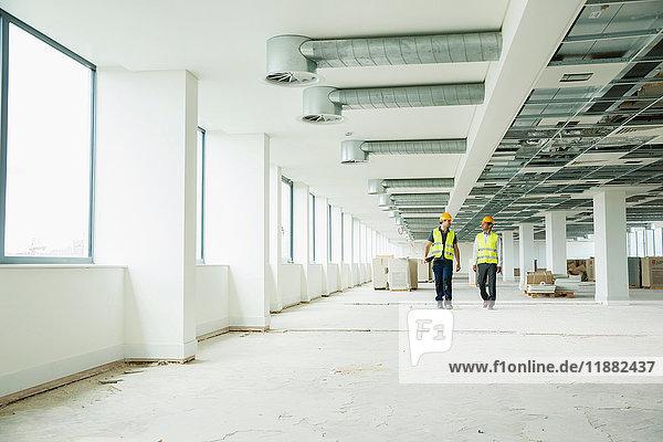 Zwei Arbeiter in Hi-Vis-Westen  die durch neu errichtete Büroräume gehen