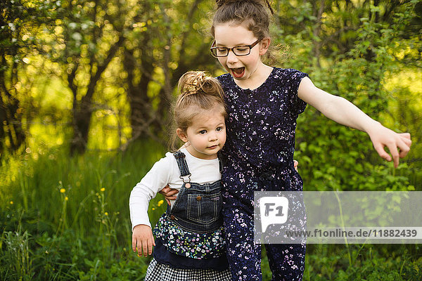 Girl and little sister playing in field with trees