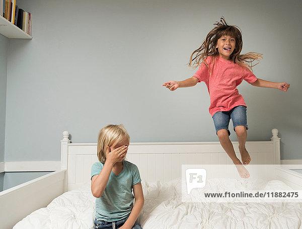 Mädchen in der Luft springt auf Bett