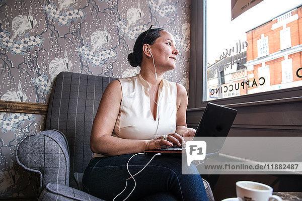 Geschäftsfrau in Kaffeebar schaut mit Laptop durchs Fenster