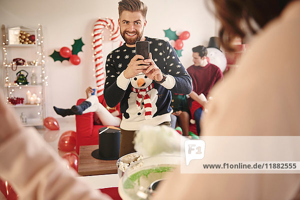 Junger Mann fotografiert Frau bei der Zubereitung von Zuckerwatte auf Weihnachtsfeier