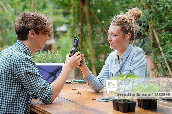 Paar mit Bier im Garten einen Toast ausbringen