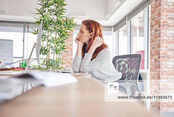 Frau sitzt am Schreibtisch und schaut weg