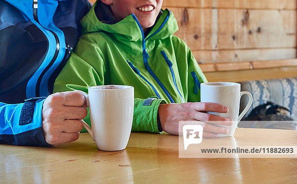 Father and son taking coffee break in log cabin  Hintertux  Tirol  Austria