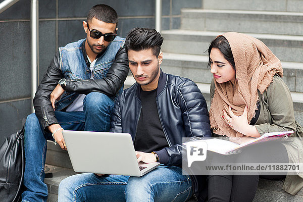 Three friends  sitting on steps  looking at laptop