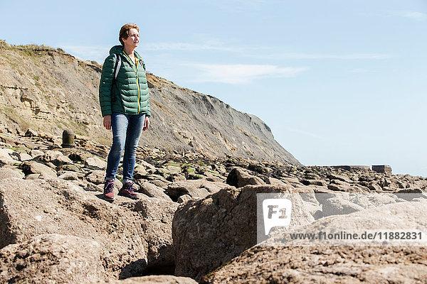 Frau auf Felsen mit Blick aufs Meer  Folkestone  UK
