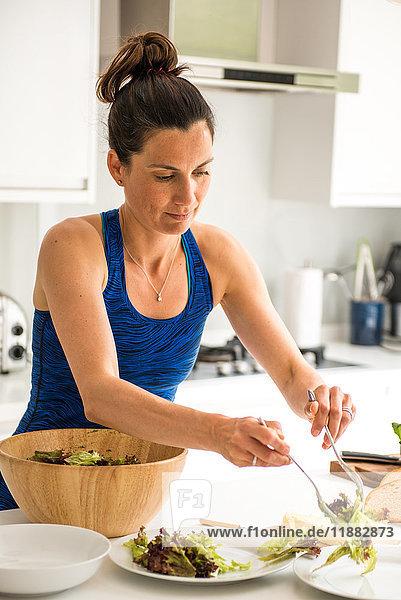 Frau bereitet Salat-Mittagessen vor