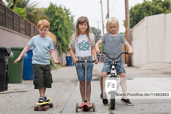 Girl and boys in lane with scooter  bicycle and skateboard