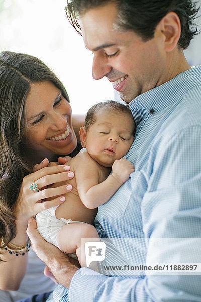 Porträt von Mutter und Vater  ein Neugeborenes haltend  lächelnd