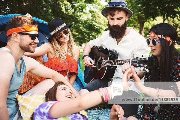 Fünf junge erwachsene Freunde spielen Akustikgitarre beim Festival-Camping