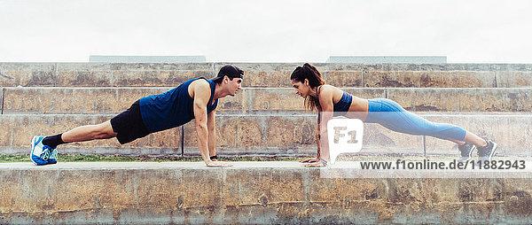 Mann und Frau trainieren im Freien  machen Liegestützen auf Stufen  South Point Park  Miami Beach  Florida  USA