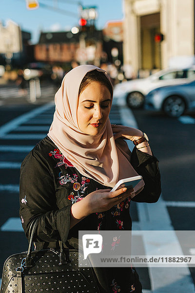 Junge Frau trägt Hijab und schaut auf Smartphone
