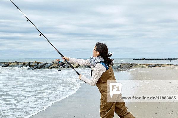 Junge Frau in Watvögeln beim Auswerfen der Meeresangel vom Strand