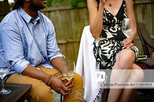 Mann und Frau beim Gartenfest  sitzend  im Gespräch  Weingläser haltend  Mittelteil