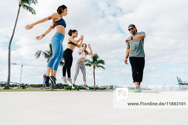 Drei Frauen trainieren mit einem persönlichen Trainer  niedrige Blickwinkel  South Point Park  Miami Beach  Florida  USA