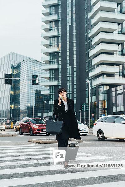 Geschäftsfrau mit mobilem und ziehendem Trolley-Gepäck  Mailand  Italien