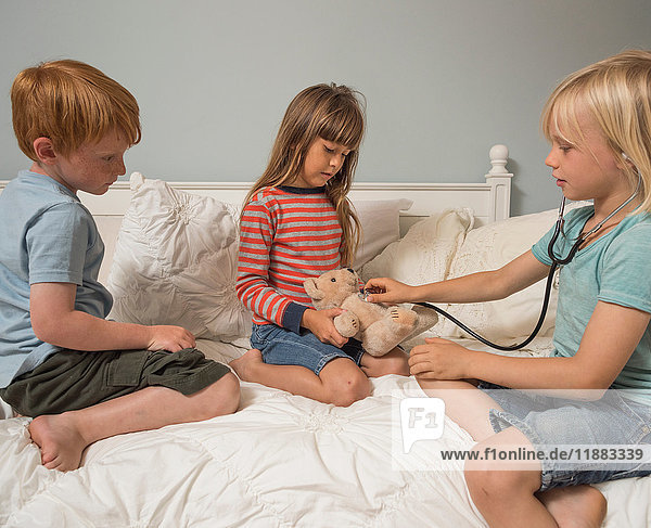 Children playing vets with stethoscope and soft toy