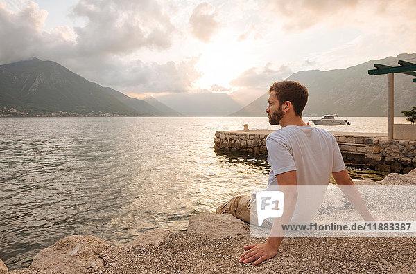 Young man sitting by water looking away  Kotor  Montenegro  Europe