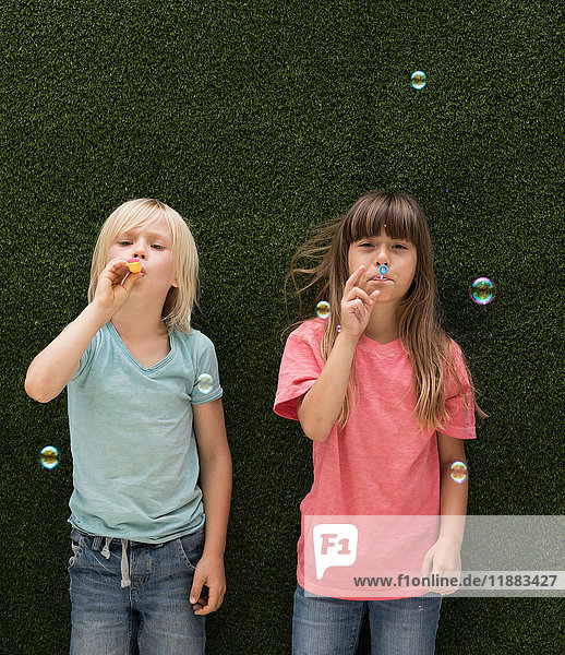 Children in front of artificial grass wall blowing bubbles