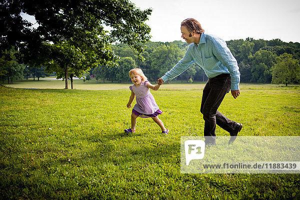 Mädchen läuft mit Vater auf dem Land
