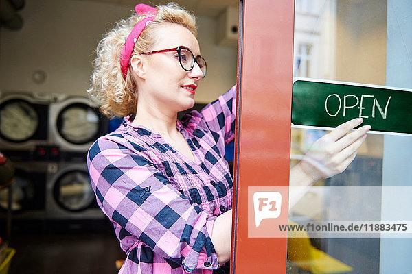 Weibliche Kleinunternehmerin hängt ein offenes Schild an der Tür des Waschsalons auf