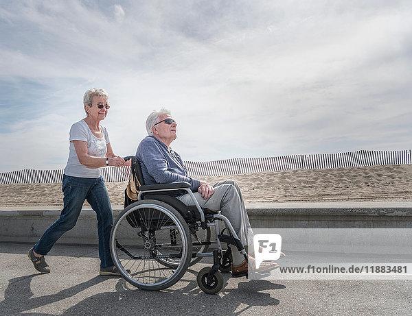 Senior woman pushing husband in wheelchair at beach  Santa Monica  California  USA