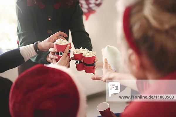 Ausschnitt einer jungen Frau  die auf der Weihnachtsfeier Popcorn verteilt