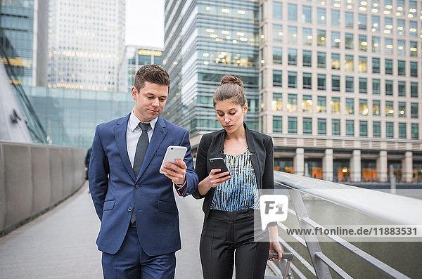Geschäftsmann und Geschäftsfrau  die ein Mobiltelefon benutzen und Gepäckwagen ziehen  Canary Wharf  London  Großbritannien