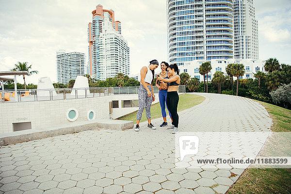 Drei Frauen tragen Sportkleidung  stehen zusammen und schauen auf ein Smartphone  South Point Park  Miami Beach  Florida  USA