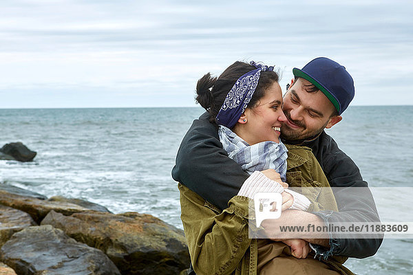 Young couple hugging on rocky beach