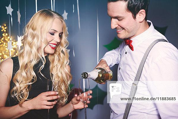 Mann und Frau auf einer Party  Mann gießt Champagner in das Glas der Frau