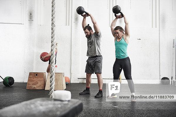Paar trainiert mit Kettlebells in einer Cross-Trainingshalle