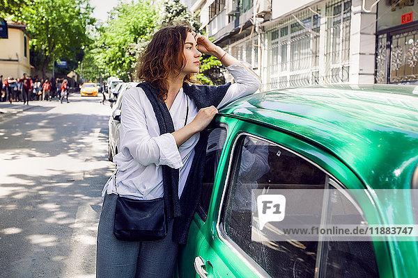 Woman beside green car