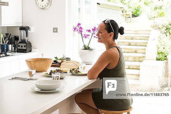 Frau sitzt an Kücheninsel und genießt Salat-Mittagessen