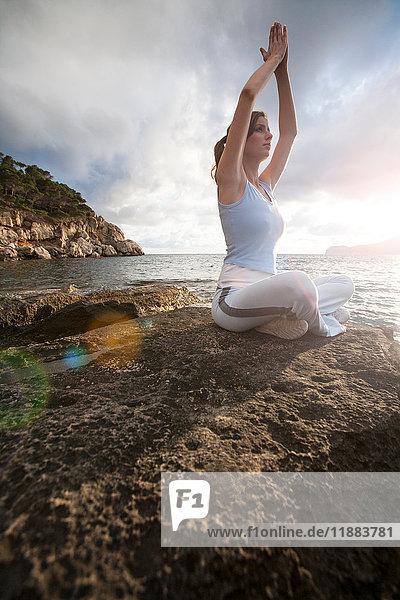 Auf Felsen sitzende Frau mit erhobenen Händen am Meer  gemeinsam meditierend  Palma de Mallorca  Islas Baleares  Spanien  Europa